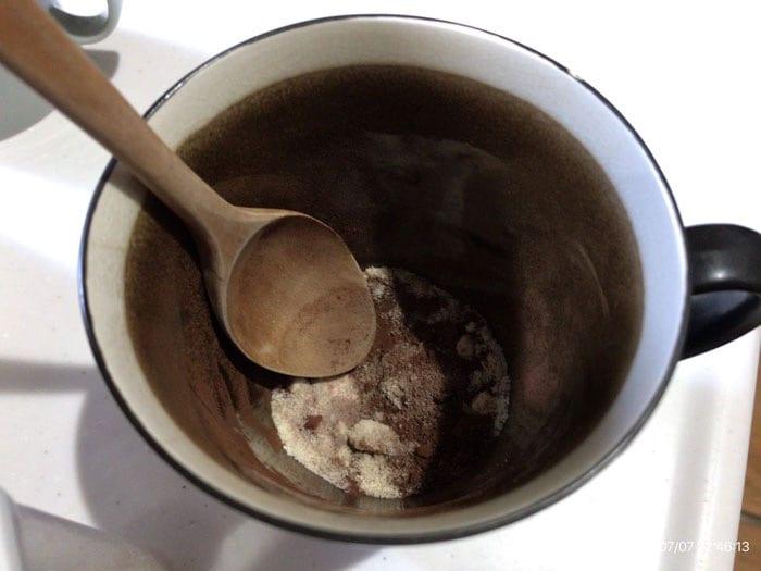 マグカップでココアと砂糖を入れて混ぜている画像